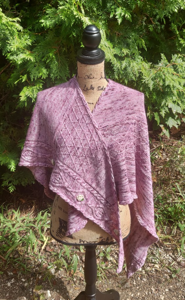 A mottled mauve shawl with purple speckles is draped over a burlap covered mannequin. One edge has a border of two twist cables and a central motif of cable framed diamonds with alternating lace leaves and crocheted roses with a small leaf. There is a criss-cross trellis section visible on each side of the shawl.